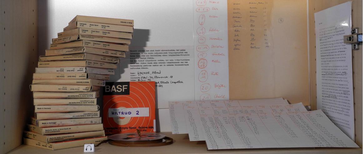 Abb.1:Regalfach zum Originalton-Hörspiel So eine Freiheit (v.l.n.r.): sämtliche Tonband-Papphüllen und eines der 21 Original- BASF-Tonbänder (enthaltend Wührs Interviews mit elf Frauen, welche das Ausgangsmaterial für die spätere Collage zum Hörspiel darstellen), handschriftliche Liste mit Namen, Alters- und Berufsangaben der interviewten Frauen, Protokoll-Liste zu den Tonbändern, eine Liste mit Vermerk der thematisch relevanten Tonband-Passagen und die Einverständniserklärung der Interviewten (© T. Betz)