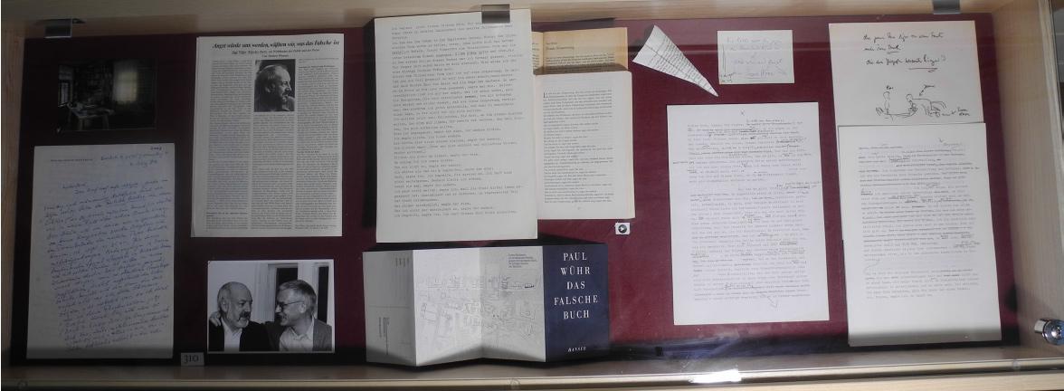 """Abb. 10: Schubfach-Vitrine zum Falschen Buch (v.l.n.r.): Foto und Brief von U. Sonnemann; Rezension (H. Wiesner), Foto (Wühr/Wiesner); Typoskript, Vorabdruck und Endfassung des Buchanfangs; Werbe-Leporello (Hanser); Typoskript mit handschriftlichen Anmerkungen zur Figuration """"Poppes' Gebet vor der Terra Nova"""", Papierflieger (aus einer FB-Seite gefaltet; die 'Erschaffung' Poppes' bzw. dessen Landung als Papierflieger: """"Poppers kommt an""""), Zeichnung zur """"Erschaffung der Terra Nova"""" (Kopulation Demeter/Rosa) (© T. Betz)"""