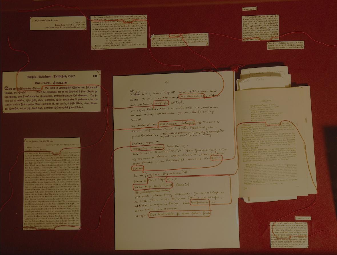 """Abb. 13: Detailansicht der Schubfach-Vitrine zu Wührs Bezugnahme auf J. G. Hamann, in der mittels eines roten Garns u.a. die Fremdbezüge/Zitate in der Figuration """"Gespräch mit dem Magus in Norden: Die Wurfschaufel"""" aus dem Falschen Buch nachvollzogen werden (v.l.n.r.): Briefe Hamanns an J. C. Lavater ( 18.01.1778) und J. G. Herder (18..05.1777), Ausschnitt aus Lavaters Physiognomischen Fragmenten zu Hamann, Original-Manuskript der 'Wurfschaufel'-Figuration, erste Seite von J. G. Hamanns Aesthetica in nuce (aus Wührs Privatbibliothek), Ausschnitte aus der Heiligen Schrift (1. Korinther 9.10, 24-27; Matthäus 2. 3. 4, 11- 12) (© T. Betz)"""