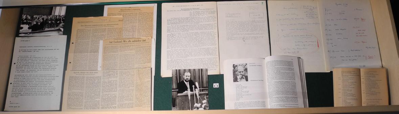"""Abb. 9: Schubfach-Vitrine zum Originalton-Hörspiel """"Preislied"""" (v-l.n.r.),: Foto (Verleihung des Kriegsblindenpreises), Begründnung der Jury, Rezensionen (W. Genanzino, H.-J. Schyle, M. Franke), Wührs Preisrede (Original-Typoskript), Foto (Wühr bei der Preisrede), ein Hörer-Protest-Brief an den NDR, der Beginn des Interviews """"Der Redefluß verschleiert"""" von K. Ramm mit P. Wühr, Manuskripte mit Notizen zu einzelnen Figurationen und zum Thema Manipulation, Reclam-Buch """"Preislied"""" (aufgeschlagen) (© T. Betz)"""